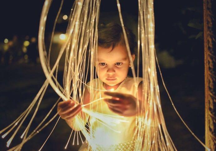 criança brinca com fios de fibra ótica